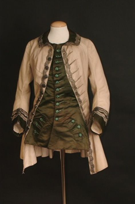 Ladie's Riding Habit. c1760-1765 fitted jacket of cream wool, w/integral waistcoat (built into the jacket) of rich olive green silk, the collar & cuffs are faced w/ matching silk. Wide silver braid & green thread covered buttons complete the garment. From the Hampshire County Council Dress Collection Image: C1999.150.
