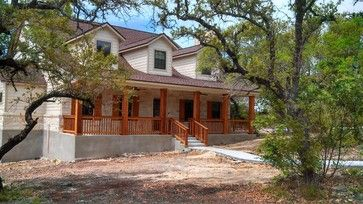 Texas Hill Country stone home with cedar columns, porch railings, and cedar shutters by Kurk Homes