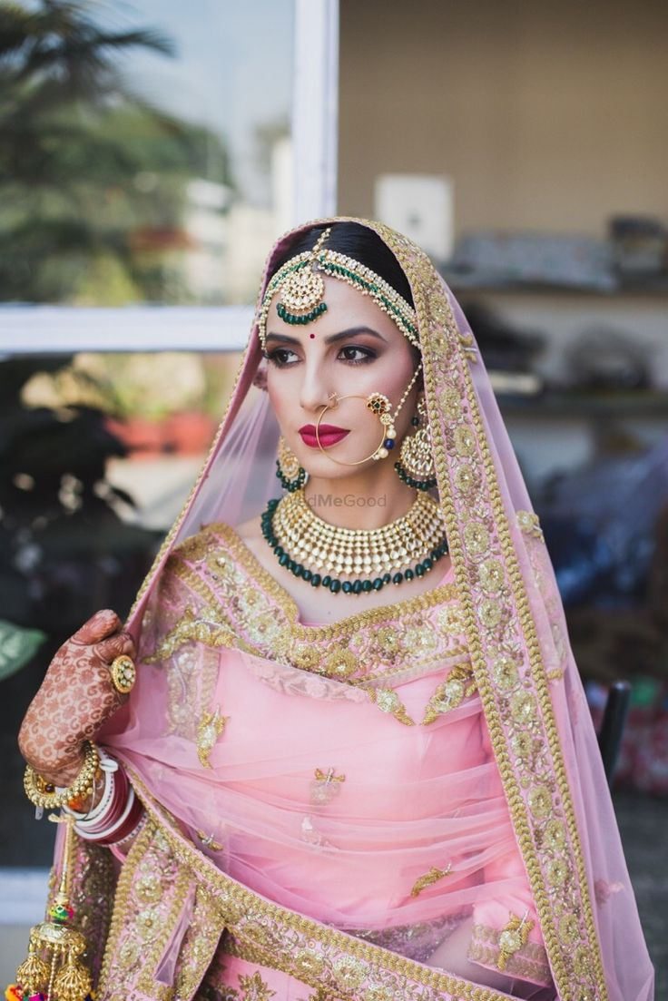Stunning bubblegum pink lehenga with emerald green jewellery for the wedding day! | WedMeGood|#wedmegood #indianweddings #jewellery #emeraldjewellery #greenandpink #pinklehenga #lightpink #lehenga #bridallehenga #traditionaljewellery #kundanjewellery
