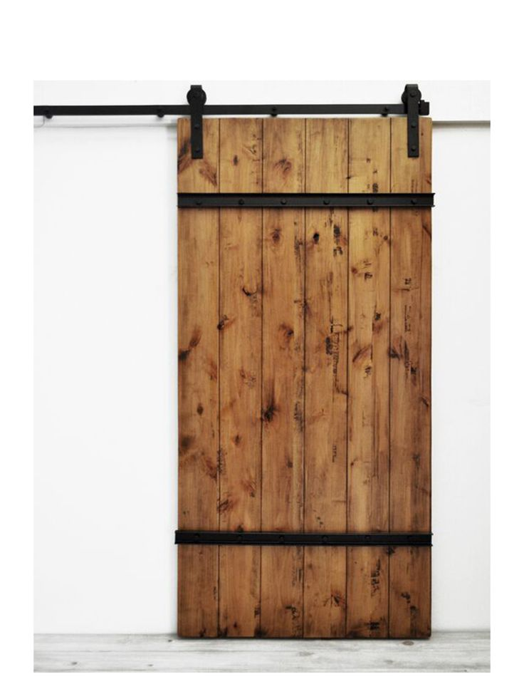 The Drawbridge Barn Door features sturdy wood planks lightly distressed and bolted together with metal plating. This style is well suited for rustic spaces, but also fits in modern applications. Made