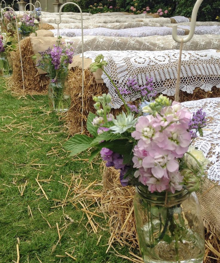 Country wedding with hay bale seating & jam jar flowers on shepherds crooks