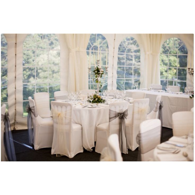 Reception marquee at Priory Bay Hotel, Ivory and silver sashes on white chair covers, table linen and silver candelabra centrepieces with pearls and fresh flowers