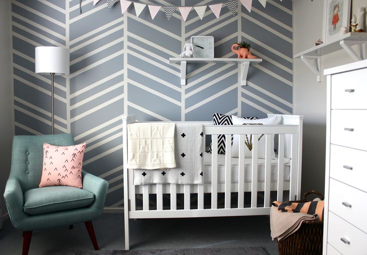 A gray, pink and white modern nursery featuring a DIY herringbone feature wall. The space is fun and flexible, but not too girly.