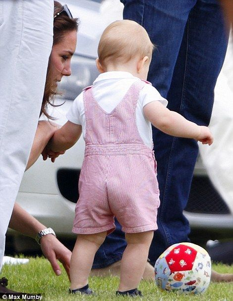 Fun and games: The little Prince George is held steady by his mother, Duchess of Cambridge