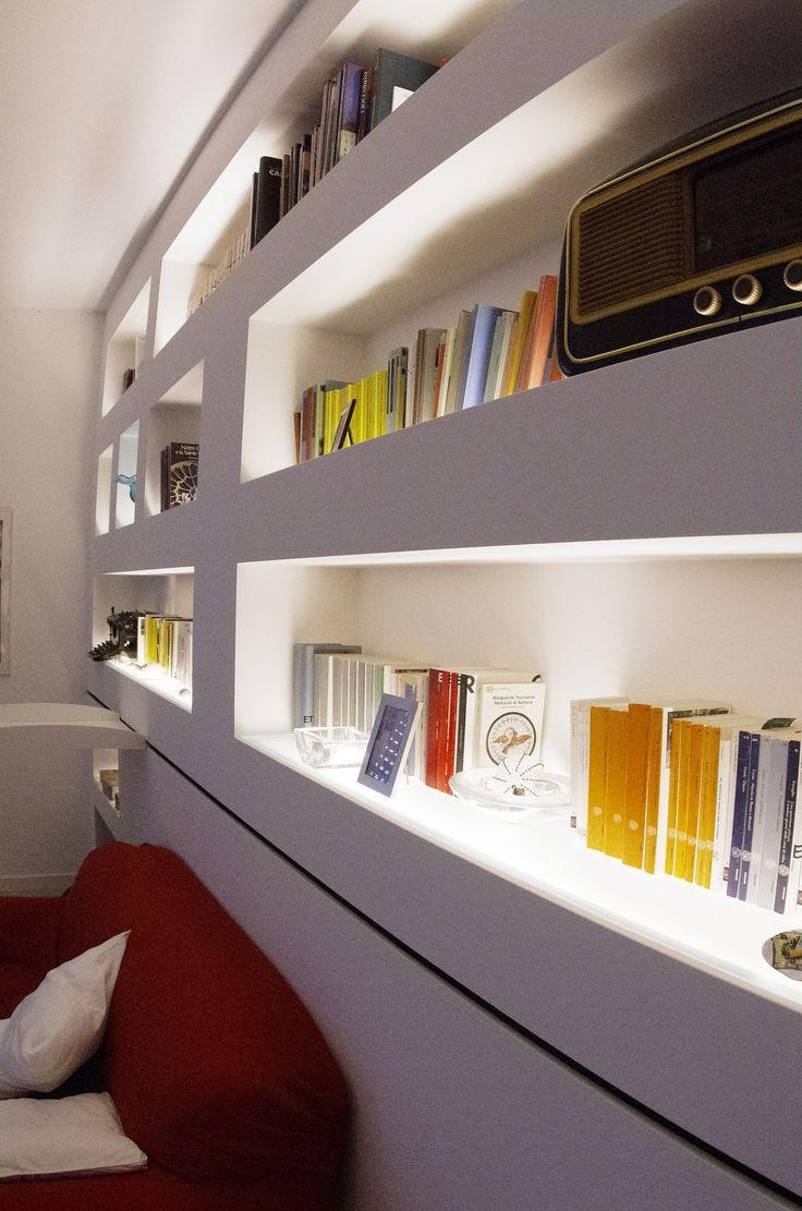 """Libreria """"MorSab""""in cartongesso retro-illuminata con sistema di Carrello-Scala scorrevole frontalmente su tutta la parete / funge anche da tavolo di servizio .  Ha la caratteristica di scorrere passando sopra al divano, permettendo così l'uso della parte libreria, soprastante. Design / Realizzazione - Lauro Ghedini & Partners"""