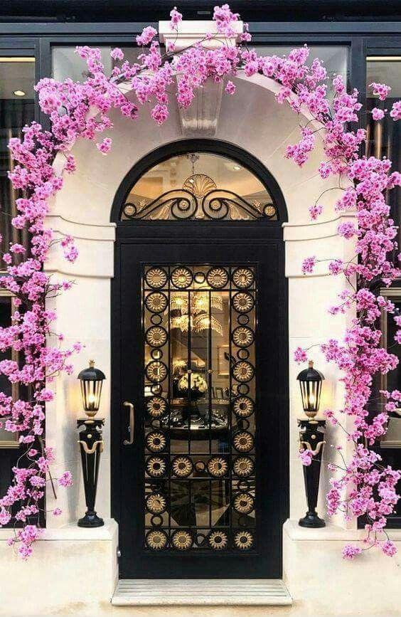 White wall, black door and pink flowers