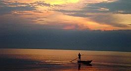 A fisherman on Lake Tanganyika watches the sun setting. Burundi