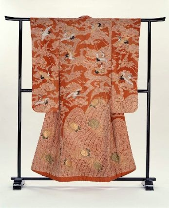 Wedding kimono (uchikake)  Japanese, Edo period, 1800–50, Silk damask (rinzu), tie resist-dyed (kaneko shibori) and embroidered with silk and couched with gold-wrapped threads, Long-sleeved outer robe (uchikake), probably for a wedding, of reddish-orange silk damask with design of tie-dyed waves at bottom embroidered with tortoises (minogame) and tie-dyed pine trees above embroidered with flying cranes (tsuru); lined with reddish-orange silk and padded at the hem. MFA