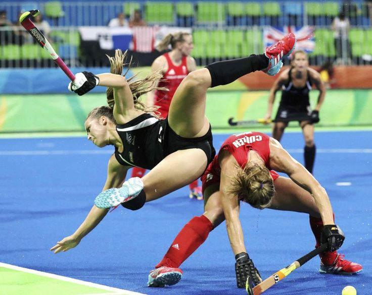 Rose Keddell of New Zealand (L) stumbles over Crista Cullen of Britain in women's field hockey semifinal. REUTERS/Vasily Fedosenko