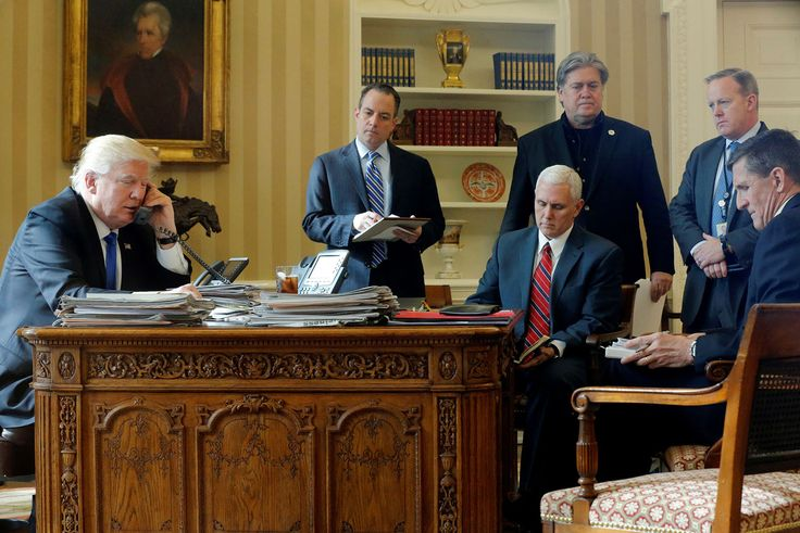 On January 28, 2017, President Donald Trump speaks by phone with Russian President Vladimir Putin in the Oval Office, joined by (from left) Chief of Staff Reince Priebus, Vice President Mike Pence, senior advisor Steve Bannon, Communications Director Sean Spicer and National Security Advisor Michael Flynn, at the White House in Washington, D.C. In the months since, Priebus, Bannon, Spicer, and Flynn all resigned or were fired.
