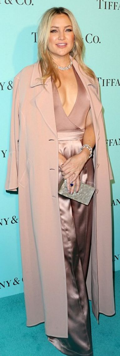 Who made  Kate Hudson's jewelry, pink coat, wrap top, pants, and tan clutch handbag?
