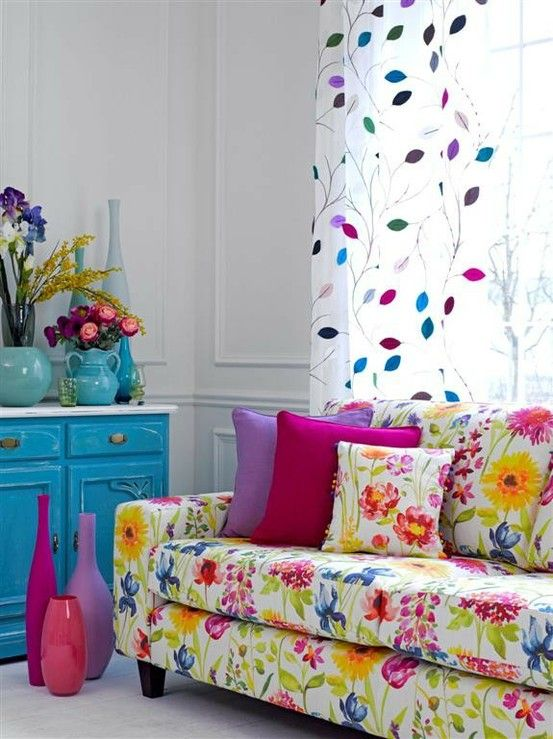 Another colorful option for a cottage.....the bright blue sideboard, the frisky window treatment and use of contemporary accessories prevent the floral sofa from looking too much like Granny's house......   Linda designinternationalstaging.com
