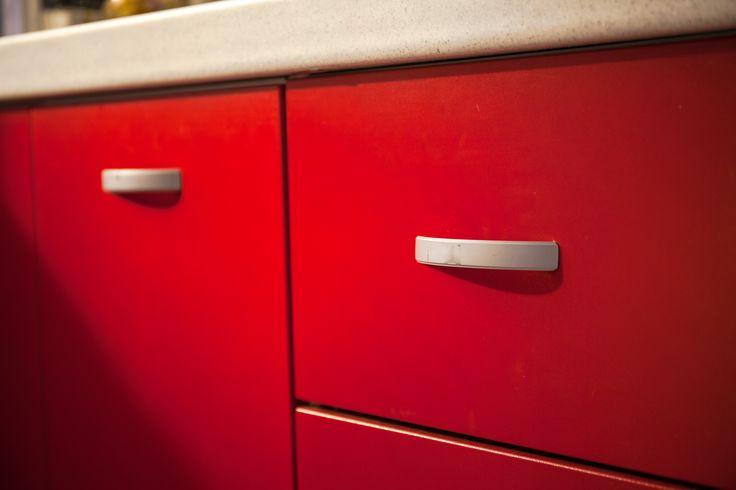 Las jaladeras color gris combinan perfectamente con la cocina color rojo.