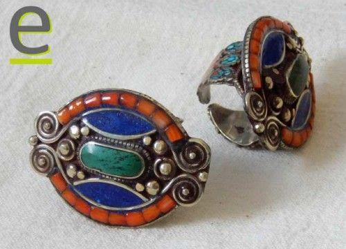 Anello tibetano con agata verde di sagoma ovale posizionata sulla lunghezza dell'anello. Decorato con corallo e pasta di corallo rosso, frammenti di turchese, pasta di lapislazzuli.