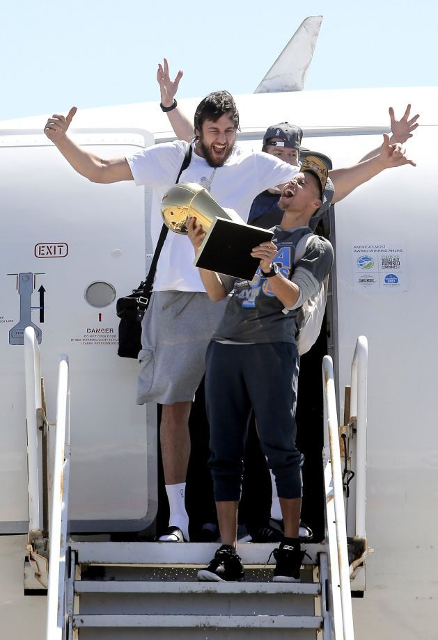 Andrew Bogut, (top) and Stephen Curry are the first off the plane with the championship trophy, as the Golden State Warriors, the 2015 NBA Champions, landed at Oakland International Airport  in Oakland, Calif., on Wed. June 17, 2015. Photo: Michael Macor, The Chronicle