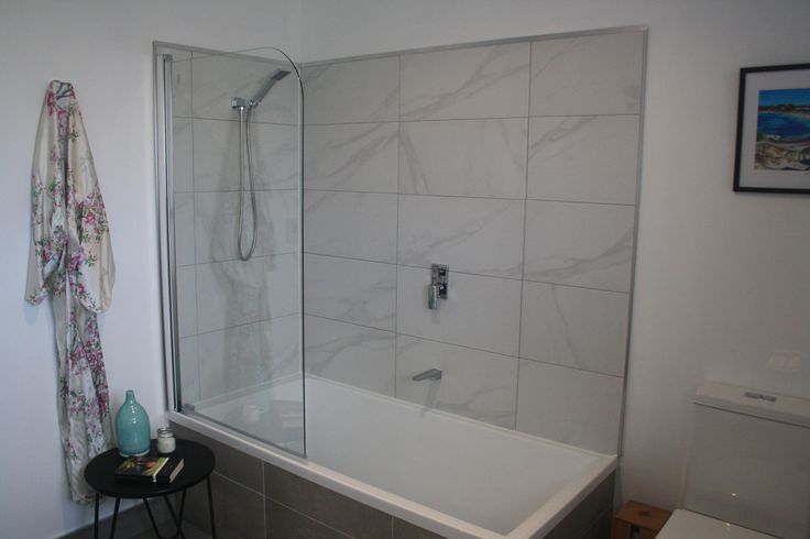 White and grey marble tiles line the new bath/shower combo in our new bathroom. turquoise hints break up the theme.
