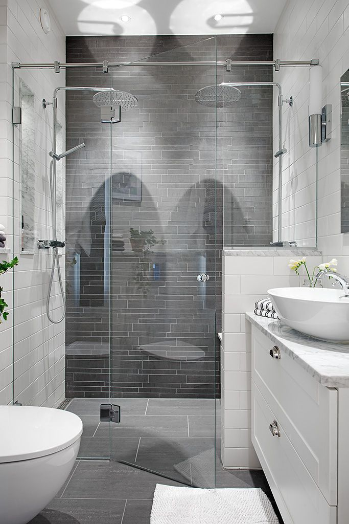 Bath - Grey tiles in an extraordinary two-person shower, the star of this room, is complemented by the Carrera marble countertop & white vessel sink.: