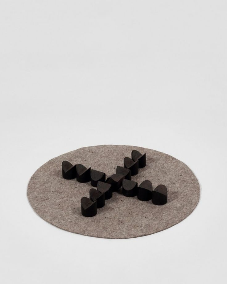 Brandub | The Souvenir Project | Tom dePaor | Shop | Design and Craft | Gifts | Makers&Brothers |   An brandub is the boardgame mentioned since the sixth century in Irish texts. The old game of ground is presented here as a section of peat, compressed and cut into thirteen figures, played on a punctured wool felt mat. An brandub, the raven, is perched at the centre of the board, outnumbered and surrounded, and plays for stalemate – an island game.