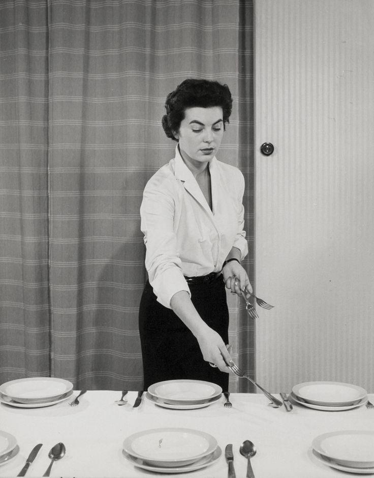 Feestdiners, tafeldekken. Vrouw dekt tafel met servies (borden) en bestek (vorm, mes, lepel). Nederland, 1950-1960.