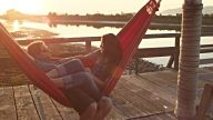 MS Husband swinging wife in hammock on dock at sunset both laughing