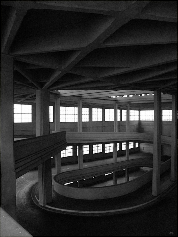 """""""The Lingotto building,Turin, Italy, once housed a Fiatfactory. Built between 1916 and 1923, the design had five floors, raw materials going in at the ground floor, and cars built on a line that went up through the building. Finished cars emerged at rooftop level, where there was a rooftop test track. It was the largest car factory in the world at the time. Le Corbusier called it """"one of the most impressive sights in industry"""", and """"a guideline for town planning""""."""""""
