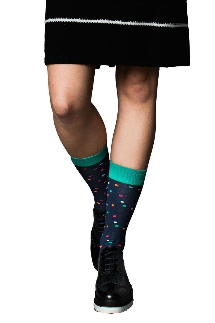 Kleurrijke sokken van Rich&Vibrant ontworpen in Zweden en duurzaam gemaakt in Turkije. Dit model Galaxy heeft een donkerblauwe ondergrond met een patroon van oranje, mintgroen, witte en roze pixels er op.
