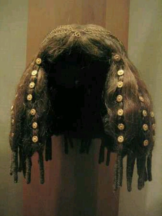 Ancient Egyptian wig from the Old Kingdom. You can tell because it is flatter up top and bulks out in the bottom with loose braids hanging, also because it is a shorter length.