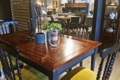 Klasyczny stół i krzesła. Krzesła drewniane z oparciem o tapicerowanym siedzisku w kolorze żółtym. Stół drewniany na 6 osób z prostymi nogami w kolorze czarnym i blatem na wysoki połysk w kolorze brązu.