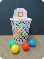 """Baby Basketball:  Find a small basket or box and 10-12 ball pit balls.  Show your child how much fun it is to put the balls into the basket, dump them out and do it again!  You can encourage counting skills, color identification, color labeling, or just learning to say the word """"ball"""" with this exciting activity."""