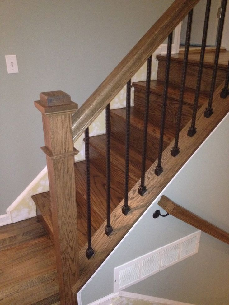 The oak post and #railing contrast eloquently with the iron spindles to attractively accent a more traditional decor. This work is by Gorsegner Brothers #Hardwood #Floors.
