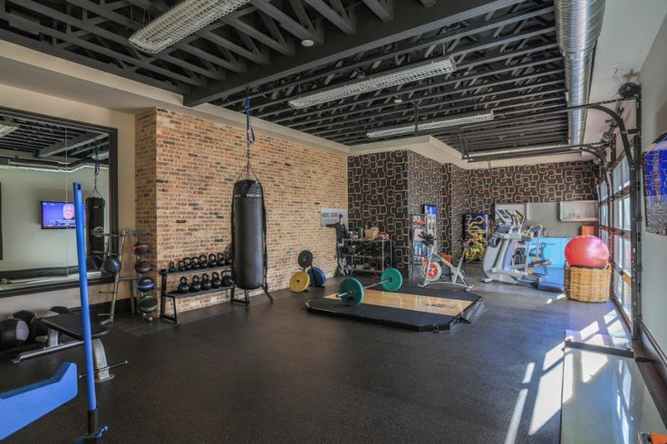 """""""Bridge Hollow Platinum Series by Mark Molthan have designed this setup above. The use of exposed graphite coloured beams and raw brick walls together with the tube lighting give an industrial modern feel to the room. The room has been sectioned off fantastically with the use of free weights, kettles, boxing equipment and cardio equipment. Heaven."""""""