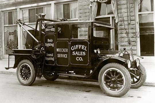 """A photograph of an early tow truck. Also called a """"wrecker"""" is utility vehicle…"""