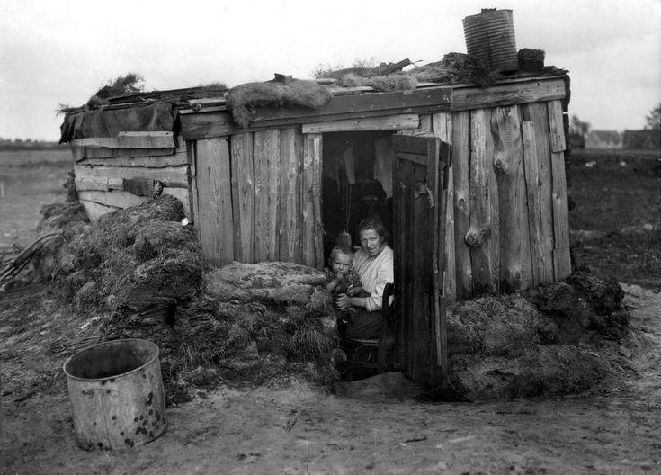 Krotten, achterbuurten, sanering: Krotwoning, plaggenhut in Drenthe [Drente], 1936. Een moeder met kind zit in de deuropening van de uit plaggen en planken gebouwde hut.