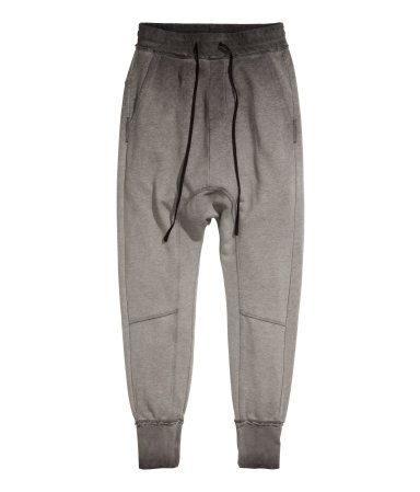 Gray/dip-dyed. Sweatpants with dropped gusset and elasticized drawstring waistband with raw edges. Side pockets, one back pocket, and decorative seams.