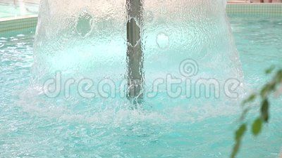Waterfall in the pool with thermal water and green branch.