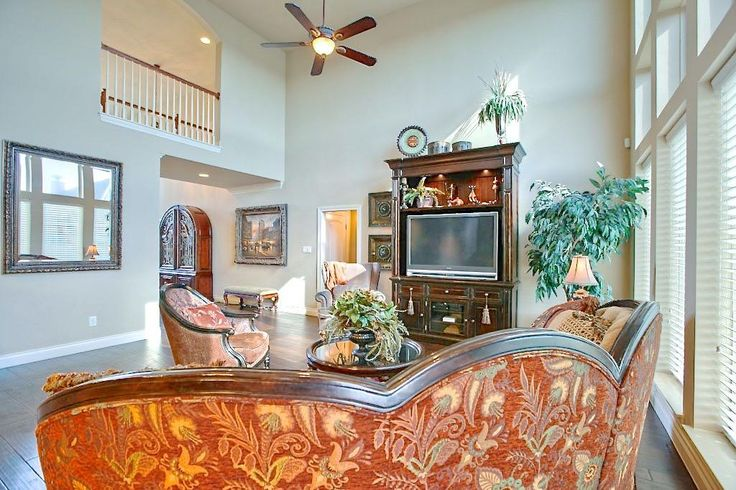 2 story family room with a view of the upstairs catwalk. Room can accommodate large furniture and has upgraded ceiling fan. Plenty of wide open space in this room.
