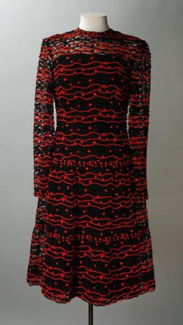 Zwart met rode namiddagjapon van tule met daarop rode en zwarte bandjes en noppen genaaid, kuitlang, lange mouwen drukknoopsluiting op rug, met losse zwarte satijnen onderjurk. Uitvoering: C.H. Kühne & Zonen, ontwerp: Maison Dior (1972), Museum Rotterdam
