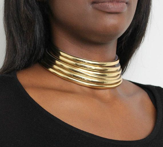 """The Gold Ndebele choker is a versatile accessory that will make you feel like royalty. Within the Ndebele tribe of South Africa the rings of the choker are called """"indzila"""" and are a symbol of a wifes bond to her husband. It is made with a light weight polymeric material and has an easy snap"""