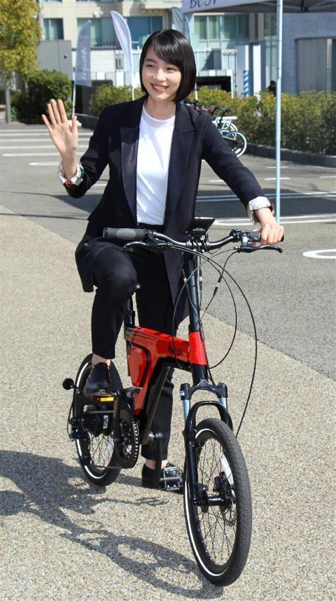 電動アシスト自転車に乗って手を振るのん=7日、東京都内