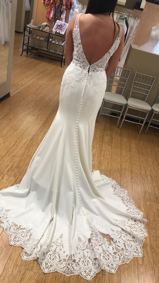 A simple silhouette with the perfect element of sexiness, this wedding gown from Essense of Australia has it all! A plunging V-neckline is the focal point of the front of this sheath silhouette and is accented with plunging side cutouts on either side. (D2503) #MichellesBride #MichellesBridalandTuxedo