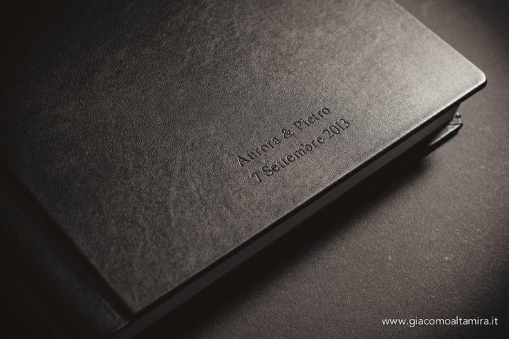 """Album in pelle nera aspetto """"nappa"""", incisione a secco con nomi degli sposi e data del matrimonio."""