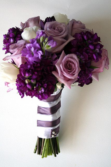 Wrapped with purple and white ribbons, this deep purple hydrangea and rose flower bouquet would be a great choice for any bride wanting a 'shades of purple' themed wedding.