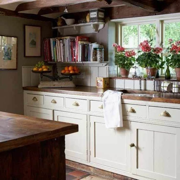Beautiful English Country Kitchen. Love the rough butcher block counters. Love the geraniums in the window.