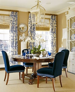 Perfect palette of camel, cream, and navy in this Boston dining room by Michael Carter of M. Carter & Co. Love the toile drapes, the oversized cream lantern, and gorgeous china cabinet with to-die-dor urn finials, the round mahogany table, and those sumptuous navy velvet chairs. Bamboo roman shades and sisal rug provide natural texture and provide a nice balance to the formality of the room.