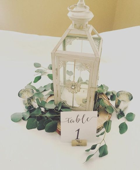lanterns decorated with eucalyptus for wedding centerpieces