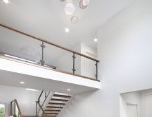 Open-to-above Foyer, wood stairs, wood and glass railing, long globe chandelier, cat walk. Custom Infill in Crestwood, Edmonton by Kimberley Homes  #infillhome #yeginfill #interiordesign #newhomedesign #homedesign #newhome #customhome #yegre #buildwithkimberley #kimberleyhomes