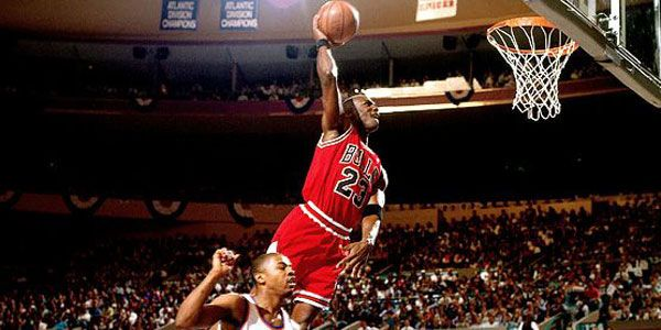 This is a picture of Michael Jordan dunking on someone. He is also one of the greatest to ever play the sport of basketball