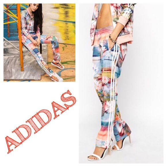 Adidas Curso d'Agua Firebird Track Pant NO TRADING The vibrant artwork on these women's Curso d'Agua Firebird Track Pants is inspired by the technicolour beauty of a Brazilian sunrise. Smooth tricot fabric, a drawcord elastic waist and 3-Stripes on the sides echo the original Firebird track pants. These pants are new, but are a floor model, inside tag has been marked to prevent return. NEVER WORN 79 cm inseam (size 36) Side zip pockets Drawcord on elastic waist Allover photo-print graphic…