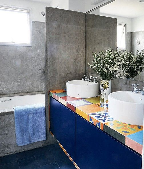 O patchwork de ladrilhos hidráulicos e o acabamento de cimento queimado refletem a preocupação com o uso de produtos sustentáveis na reforma do banheiro de casal, feita pela arquiteta Adriana Yazbek. As cubas redondas de sobrepor são brancas e não brigam