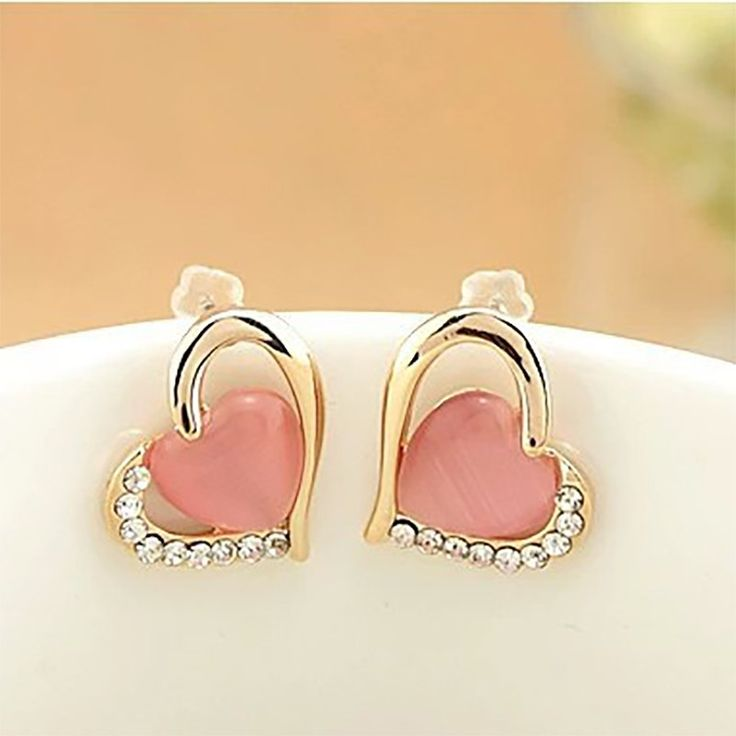This pair of stud earrings is heart - shaped and composed with golden colour with a coloured pearl.